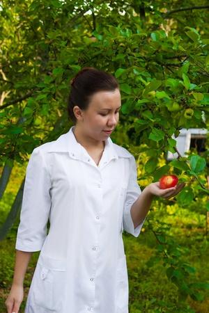Un médico mujer bonita entrega de una manzana en el jardín de manzana