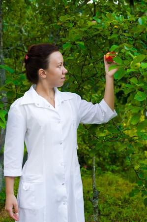 Doctor sonriente feliz con manzana en el jardín, con manzanos