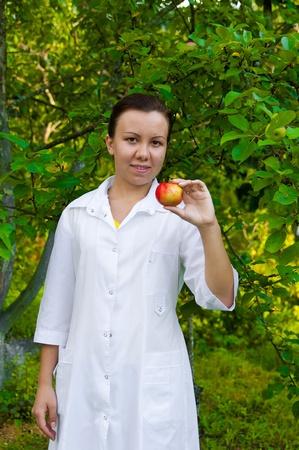 Un m�dico de mujer bonita entrega una manzana en el jard�n manzana Foto de archivo