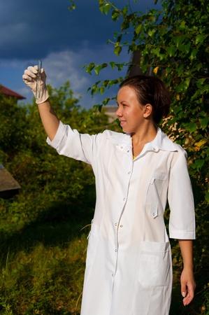 mujer joven médico en uniforme con el exterior de tubo de ensayo Foto de archivo
