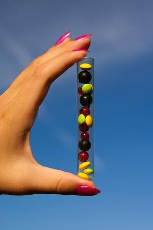 tubo de ensayo con diferentes pastillas multicolores, las bayas de grosella y al aire libre de plantas en el jard�n