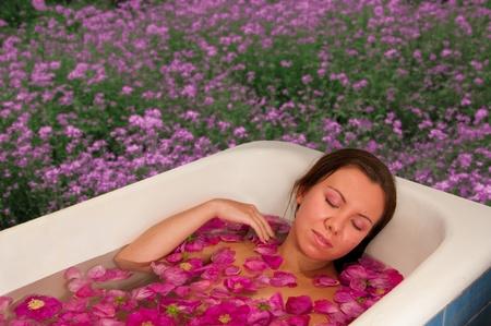 bella mujer disfrutando de baño con pétalos de rosa al aire libre