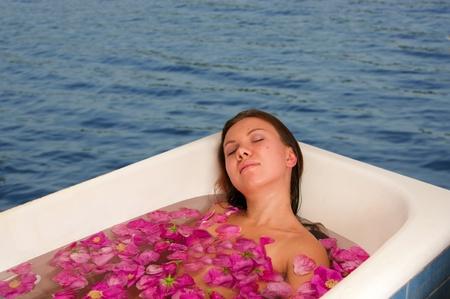hermosa mujer disfrutando de ba�o con p�talos de rosa al aire libre Foto de archivo