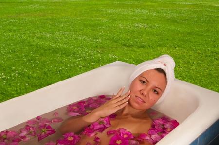 hermosa mujer disfrutando de baño con pétalos de rosa al aire libre Foto de archivo