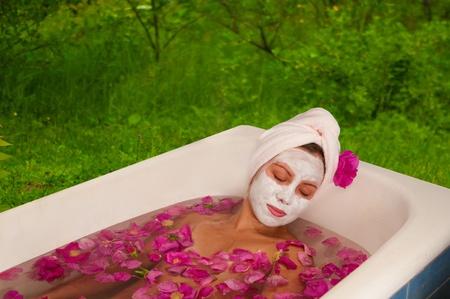 beautiful woman enjoying bath with rose petals outdoors photo
