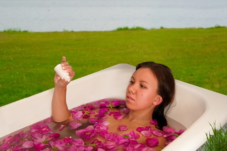 mujer hermosa que disfruta de baño con pétalos de rosa al aire libre Foto de archivo
