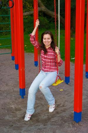 sonriendo feliz joven balanceándose en el patio de