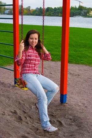 sonriente mujer joven feliz que hace pivotar en patio de recreo