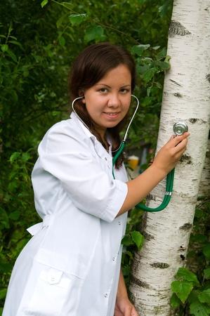 Mujer joven que escucha a un árbol con un estetoscopio Foto de archivo