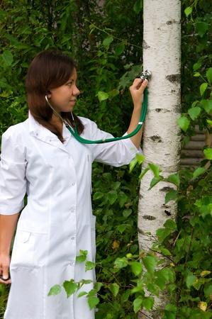 Mujer joven escucha a un árbol con un estetoscopio Foto de archivo