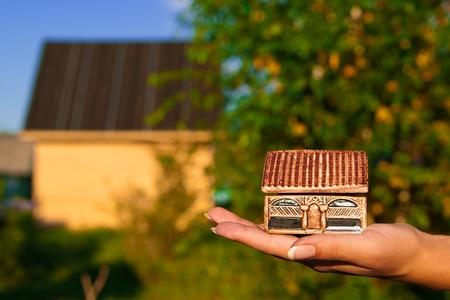mujer que sostiene una casa miniatura en la mano en el fondo de una casa real.