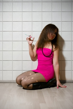 whore: girl dressed like hooker sitting with syringe in hand and looking aside Stock Photo