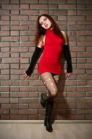 ni�a vestida como prostituta posando cerca de la pared de ladrillo Foto de archivo