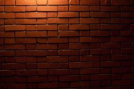Rojo ladrillo textura de la pared con una luz de arriba hacia abajo