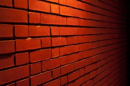 Pared de ladrillo rojo de textura con una luz de arriba hacia abajo Foto de archivo