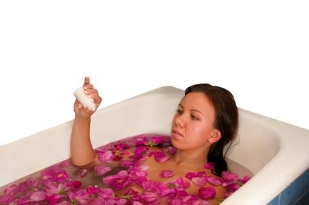 bella mujer disfrutando de ba�o con p�talos de rosa aisladas en blanco Foto de archivo