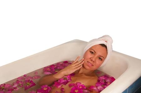 mujer hermosa que disfruta del ba�o con p�talos de rosa aislados en blanco