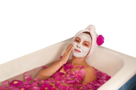 hermosa mujer disfrutando de baño con pétalos de rosa aislados en blanco