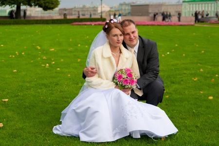 el novio y la novia se sienta junto en el jardín