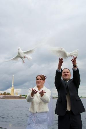 novio y la novia con unas palomas de vuelo