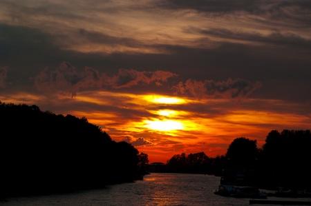 dorada puesta de sol sobre el río. Cielo con nubes