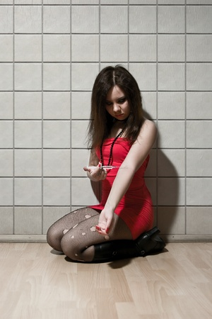 girl dressed like hooker sitting with syringe in hand and doing injection photo