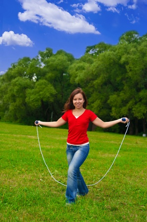 Young woman with skipping rope on the lawn photo
