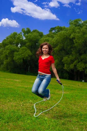 Young woman with skipping rope on the lawn Stock Photo