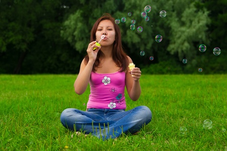 Gorgeous young brunette girl blowing soap bubbles in sunlit park photo