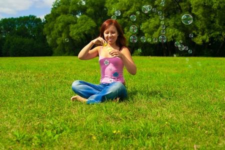 Joven morena chica soplando pompas de jabón en forma de casa Foto de archivo