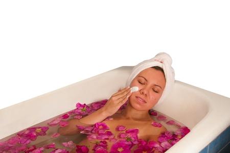 bella mujer disfrutando de baño con pétalos de rosa aisladas en blanco Foto de archivo