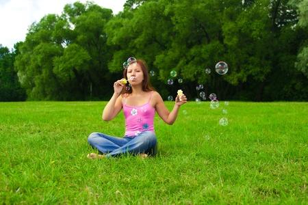 Hermosa joven muchacha morena haciendo pompas de jabón en el parque iluminado por el sol