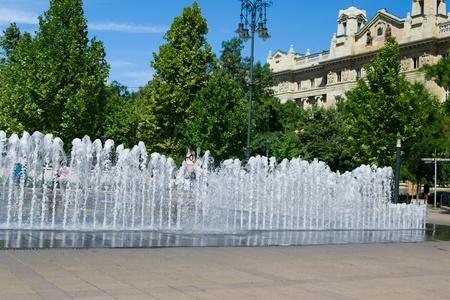Fuente en Budapest en verano con un edificio histórico en el fondo