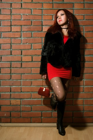 girl dressed like hooker posing near brick wall photo