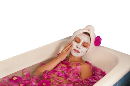 beautiful woman enjoying bath with rose petals isolated on white photo
