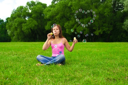 young brunette girl blowing soap bubbles in shape of heart photo