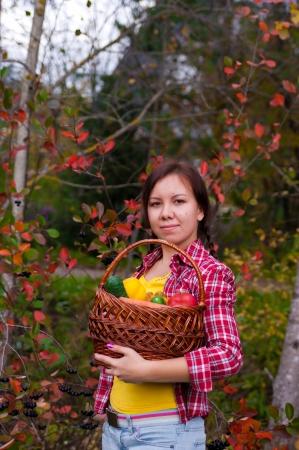 Muchacha que sostiene una cesta de verduras en el jard�n Foto de archivo