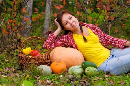 Chica tumbada en el c�sped cerca de canasta de verduras