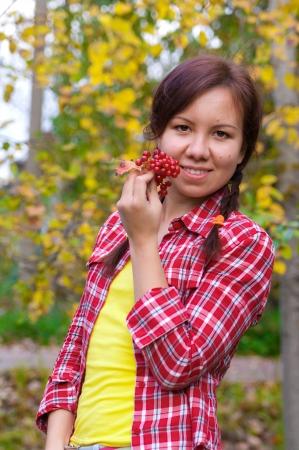 arrow wood: Muchacha que sostiene un racimo de bayas rojas de madera arrow Foto de archivo