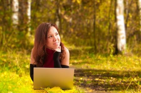 Mujer atractiva joven que miente con la computadora port�til en el fondo del oto�o