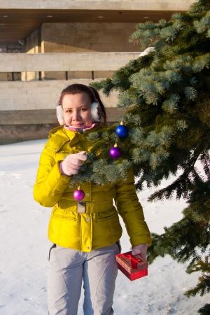 muchacha adorna el �rbol de navidad al aire libre Foto de archivo