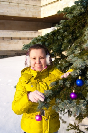 girl decorating christmas tree outdoors Stock Photo - 17098133