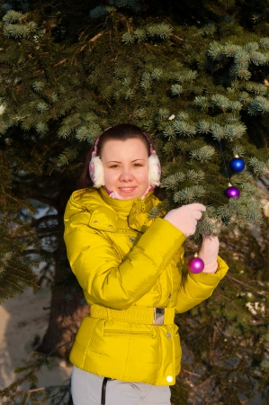 girl decorating christmas tree outdoors Stock Photo - 17098135