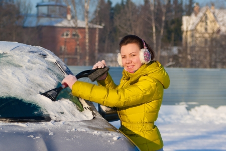 Chica limpieza de ventanas de coche de la nieve Foto de archivo
