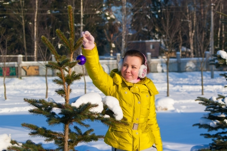 girl decorating christmas tree outdoors Stock Photo - 17098130