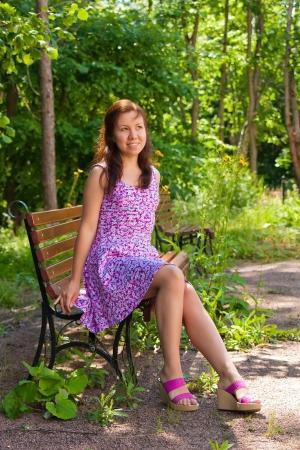 mujer sentada en el parque y mirando hacia afuera