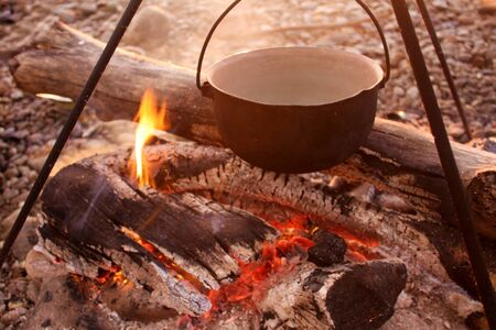Tourist breakfast at dawn. Bonfire, bowler with food and tripod. Wooden firewood, coals, summer on nature in the forest. Delicate colors of the morning sun