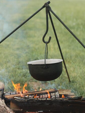 Camping outdoors. Cooking in a bowler hat hung on a tripod over a burning fire on the background of grass and chipped firewood