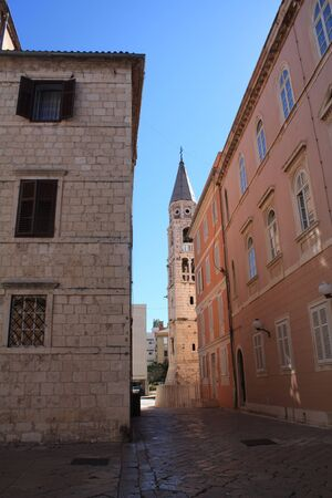 Narrow streets of a European city with red roofs and stone walls. A platform of stone and a shadow in the city. A chapel in the distance among tall houses