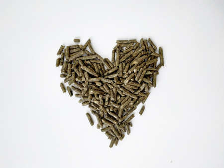 Food green pellets for a hamster, rabbit, guinea pig, mouse, chinchilla, degu. Food pellets for a rodent isolated on a white background. Heart shaped veggie food on a white background. Green healthy pellets feed, nutrition, pet food